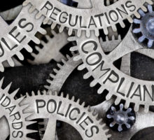 Gears with words on them: compliance, regulations, policies, standars